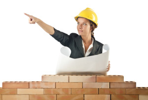 Businesswoman with drawings near brick wall