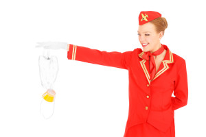 A picture of an attractive stewardess presenting an oxygen mask over white background