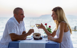 Couple in sea restaurant at sunset