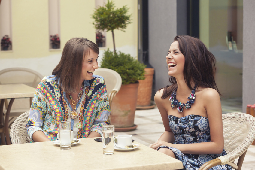 Two girlfriends having coffee and laughing