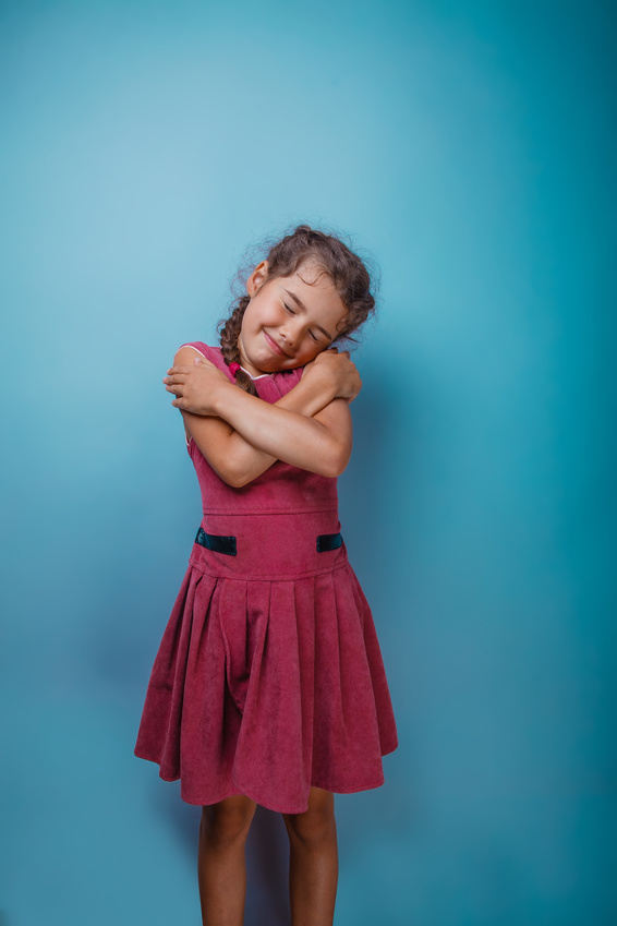 Girl seven years old, European-looking brunette in a pink dress hugging herself shoulders closed her eyes on a gray background, smiling, sleeping